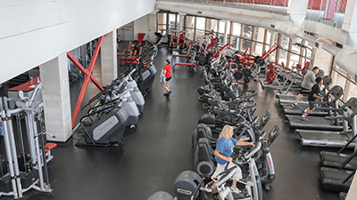 fitness room with people working out on various machines