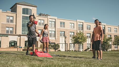 Students playing cornhole in the quad