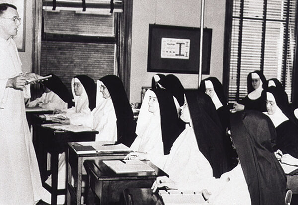 Black and white picture of the sisters in a classroom learning about theology