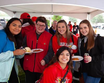 Alumni posing in the Homecoming tent
